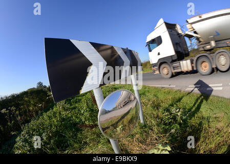 lorry passing warning sign of sharp bend and circular safety mirror to give drivers emerging from junction view - Stock Photo