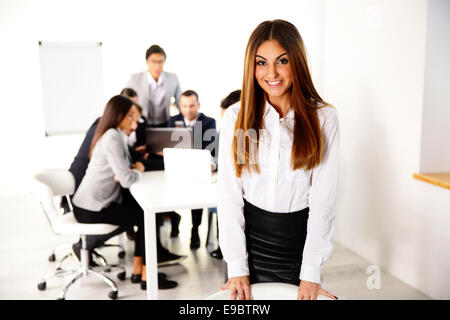 Portrait of a happy businesswoman in front of business meeting - Stock Photo