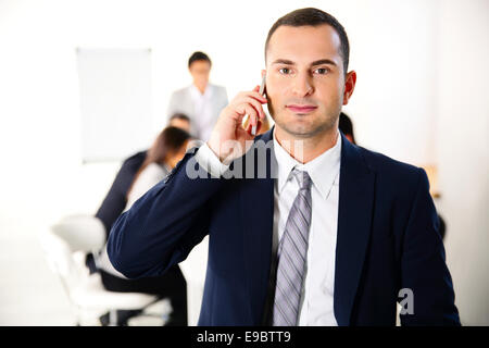 Businessman talking on the smartphone in front of business meeting - Stock Photo