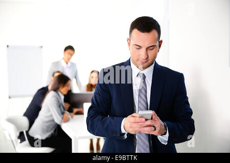 Businessman using smartphone in front of business meeting - Stock Photo