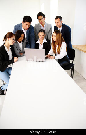 Group of a business partners using laptop together - Stock Photo