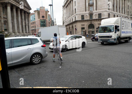 A City of London dangerous cyclist courier about to push his way through busy traffic cars and lorries congestion - Stock Photo