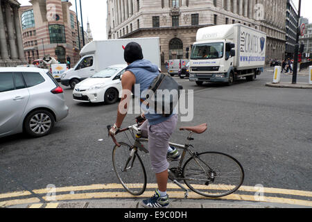 A City of London cyclist courier preparing a dangerous move about to push his way through busy traffic congestion - Stock Photo
