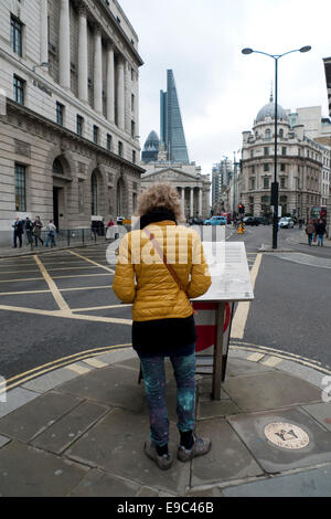 London, UK. 24th October, 2014. At Bank intersection of 5 roads in The City of London a pedestrian tourist checks - Stock Photo