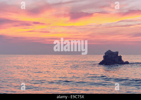 rock at sunset on the sea with pink colors - Stock Photo