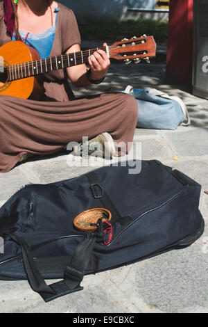 Girl playing guitar on the street. Girl who sings - Stock Photo