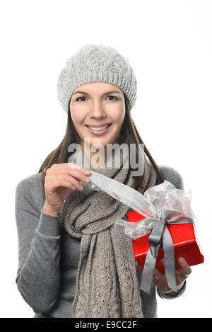 Close up Pretty Smiling Young Woman in Winter Fashion Holding Gift Box While Looking at Camera, Isolated on White - Stock Photo