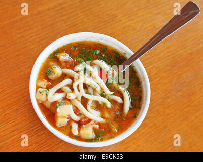 Crimean tatar cuisine - top view of laghman soup in white bowl - Stock Photo
