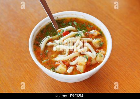 Crimean tatar cuisine - laghman soup in white bowl - Stock Photo