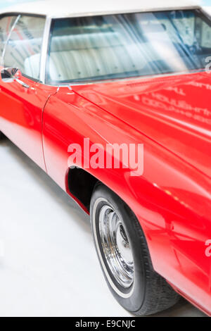 Close Up Detail of Shiny Red Classic Car in Studio with Focus on Wheel, Hood, and Windshield. - Stock Photo