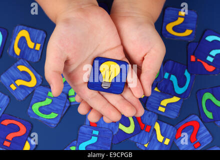 Yellow light bulb in child's hands on blue background with a lot of question marks. Pictures drawn by me. - Stock Photo