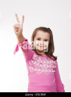 girl showing victory sign with her hand - Stock Photo