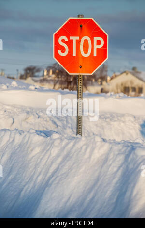 A stop sign  buried in a deep snow bank. - Stock Photo