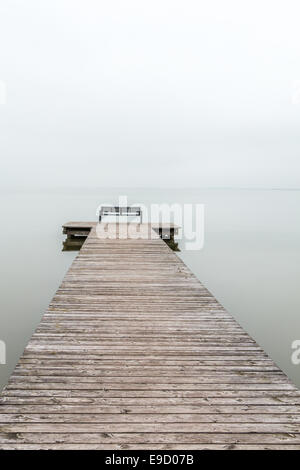Jetty in foggy weather with bench at end (vertical) - Stock Photo