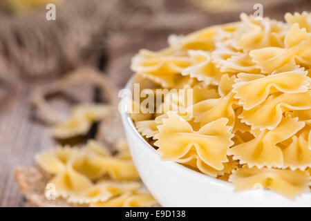 Farfalle (commonly known as Bow-Tie Pasta) in a bowl on wooden background - Stock Photo