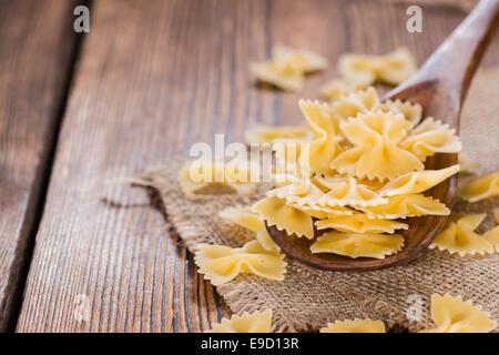 Farfalle (commonly known as Bow-Tie Pasta) on a wooden spoon - Stock Photo