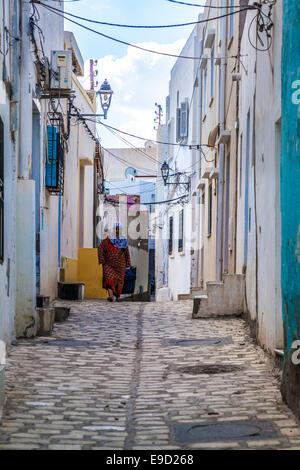 Elderly Arab woman walks along a narrow cobbled sidestreet  in the medina in Sousse,Tunisia. - Stock Photo
