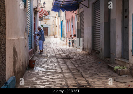 A man collects laundry from a house down a sidestreet in the medina at Sousse, Tunisia while two others chat on - Stock Photo