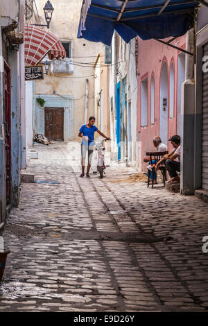 Young man walks his moped down a narrow cobbled sidestreet in the Medina in Sousse,Tunisia while two others chat - Stock Photo