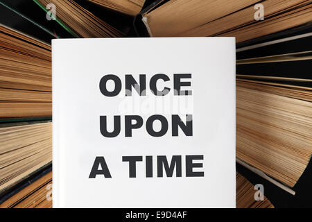 Top view of old hardback books with book 'Once Upon A Time' - Stock Photo