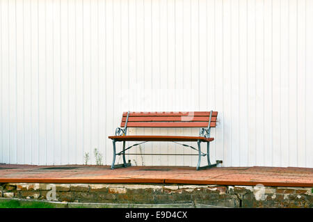 A single red wooden park bench on an outdoor patio in front of a white wall that is splashed with red paint behind - Stock Photo