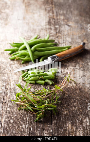 french beans and summer savory on wood - Stock Photo