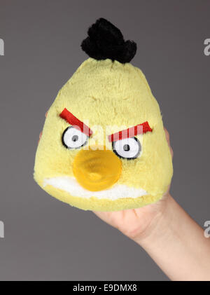 Tambov, Russian Federation - September 11, 2013 Human hand with yellow Angry Birds soft toy on gray background. - Stock Photo