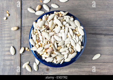 Mixed salted nuts and seeds on a wooden table - Stock Photo