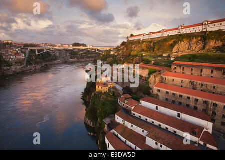 Picturesque city of Porto at sunset in Portugal. Wine cellars and warehouses on a steep shore of the Douro river. - Stock Photo