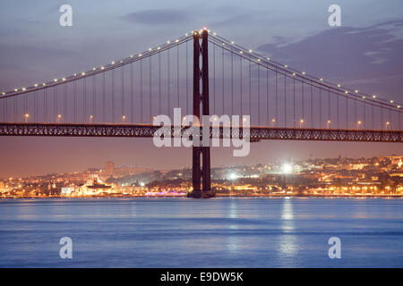25th of April (Portuguese: Ponte 25 de Abril) Bridge over Tagus river at night and city of Lisbon, Portugal in the - Stock Photo