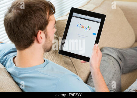 young man looking at Google website on an iPad - Stock Photo