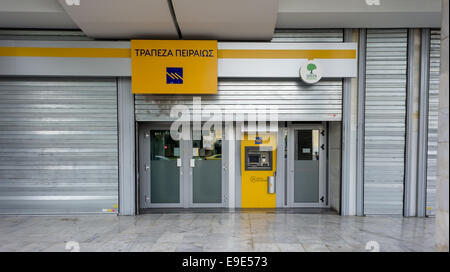 Athens, Greece. 26th October 2014. A branch (closed for Sunday) of Piraeus Bank, the largest bank in Greece, is - Stock Photo