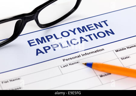 Employment Application form with glasses and ballpoint pen - Stock Photo