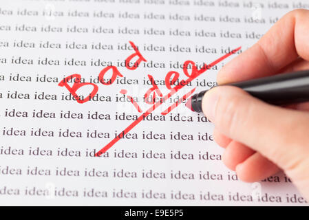 Woman's hand with red pen writing words 'Bad idea' on the background of words 'idea'. - Stock Photo