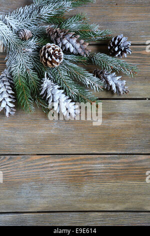 Xmas fir branch with cones on wooden boards, christmas background - Stock Photo