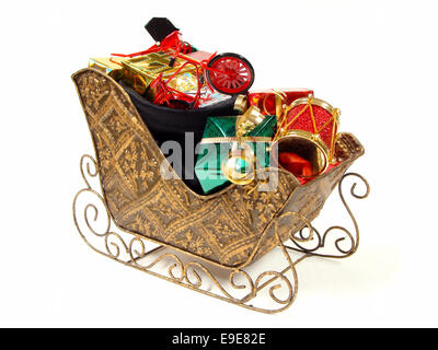 Christmas sleigh filled with a bag of gifts and toys over a white background - Stock Photo