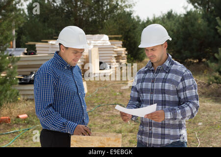 Two engineers having a discussion on site as they stand discussing a document with stacks of insulated wooden panels - Stock Photo