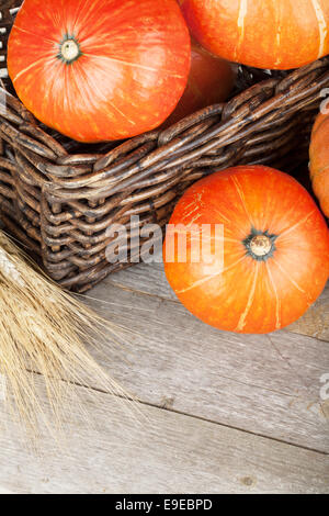 Ripe small pumpkins in basket on wooden table background - Stock Photo