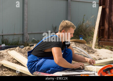 Workman on a building site taking a right angle measurement as he measure a wooden insulated beam before cutting - Stock Photo