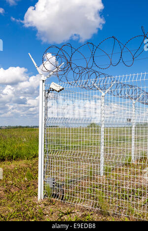 Fence with barbed wire on blue sky background - Stock Photo