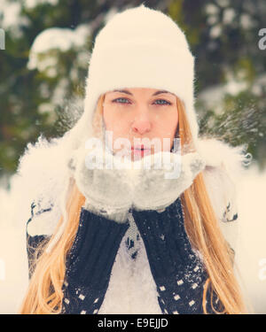 Beautiful blond woman blowing snow outdoors - Stock Photo