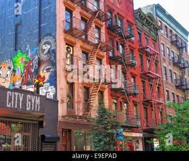 Brick building with fire escape stairs and graffiti in New York - Stock Photo
