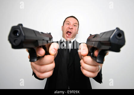 a man with two guns dressed in a black suit and tie shoots guns at the camera - Stock Photo