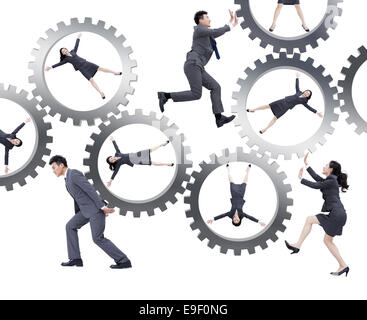 Young business people pushing gear - Stock Photo