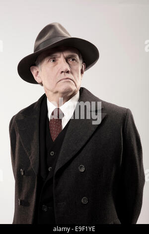 old characterful man in trilby hat and long coat looking like a detective / policeman / gangster in costume shot - Stock Photo