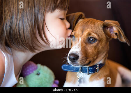 Toddler girl kissing her puppy dog - Stock Photo