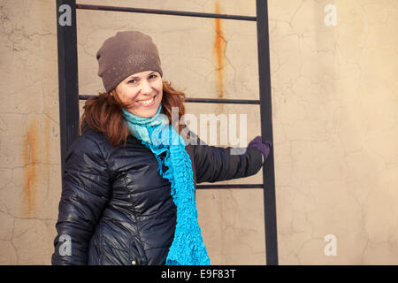 Outdoor portrait of young smiling Caucasian woman near to black metal ladder on the roof - Stock Photo