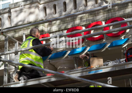 London, UK. 27th October, 2014. Workers on scaffolding repair the signage above a Tesco supermarket branch in Wimbledon. - Stock Photo