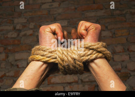 Hands tied up with rope - Stock Photo