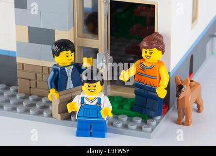 Tambov, Russian Federation - January 08, 2014 Happy LEGO family standing near his home with dog. - Stock Photo